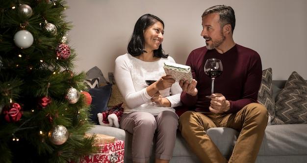 Frau, die ihrem überraschten ehemann ein geschenk gibt