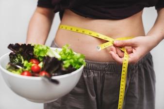 Frau, die ihren Bauch und Gewicht misst