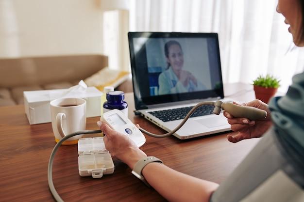 Frau, die ihren blutdruck mit elektronischem tonometer zu hause unter kontrolle des virtuellen arztes misst