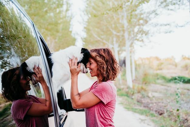 Frau, die ihren border-collie-hund in einem van umarmt. reisekonzept