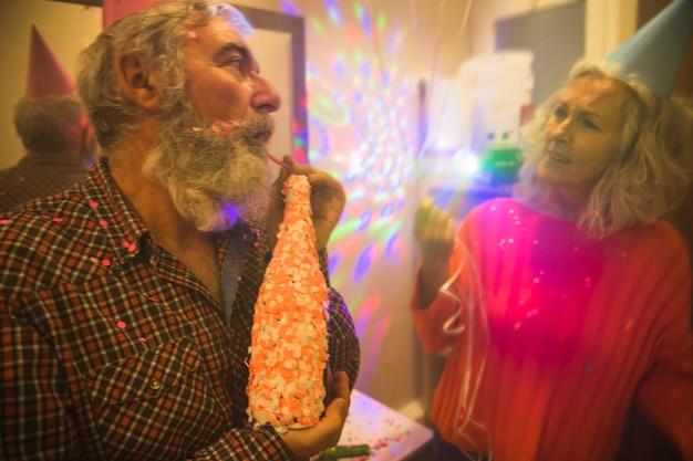 Frau, die ihren ehemann hält die alkoholflasche verziert mit konfetti in der geburtstagsfeier betrachtet