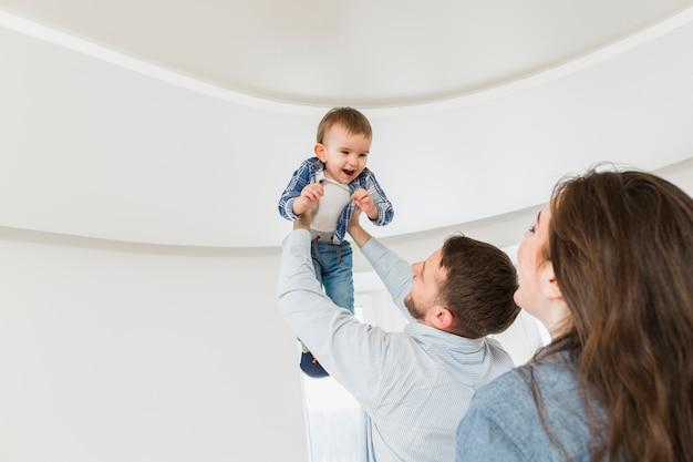 Frau, die ihren ehemann trägt ihren babysohn in den händen betrachtet