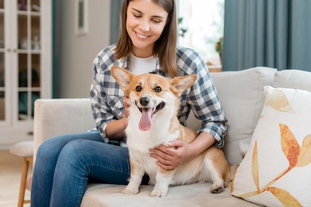 Frau, die ihren entzückenden hund auf der couch hält