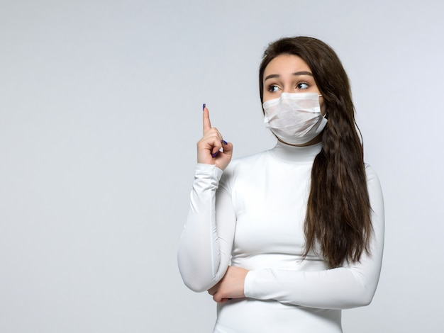 Frau, die ihren finger im weißen kleid und in der weißen medizinischen sterilen schutzmaske hervorhebt