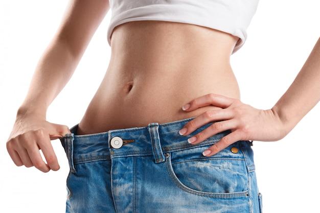 Frau, die ihren fortschritt nach gewichtsverlust zeigt