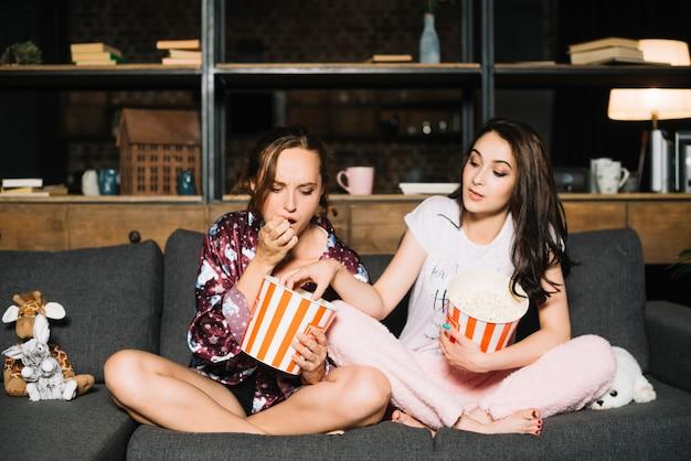 Frau, die ihren freund betrachtet, der popcorn von ihrem eimer nimmt
