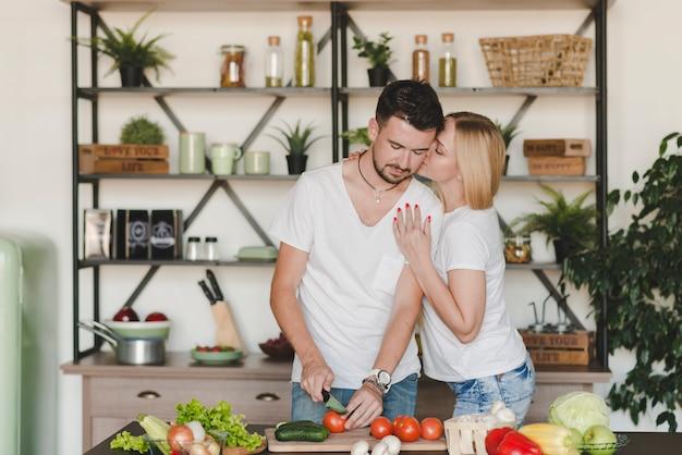 Frau, die ihren freund schneidet rote tomate mit messer küsst