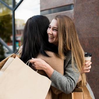 Frau, die ihren freund umarmt, während einkaufstaschen halten