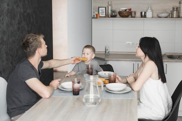 Frau, die ihren fütterungsmais ihres ehemanns zu ihrem sohn betrachtet