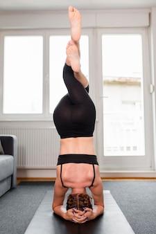 Frau, die ihren gleichgewichtssport zu hause konzept hält