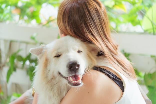 Frau, die ihren großen hund, glück und freundschaft ihrer hundefreundlichen haustiernahaufnahme umarmt