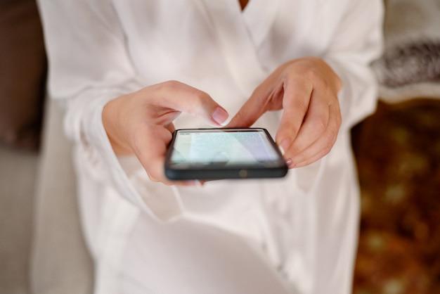Frau, die ihren handy bei der aufwartung in weiße pyjamas konsultiert.