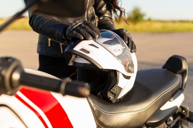 Frau, die ihren helm auf ihr motorrad setzt