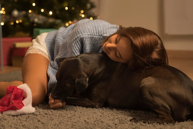 Frau, die ihren hund an weihnachten liebt