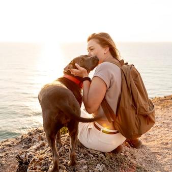 Frau, die ihren hund bei sonnenuntergang umarmt