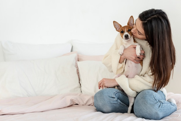 Frau, die ihren hund hält und küsst