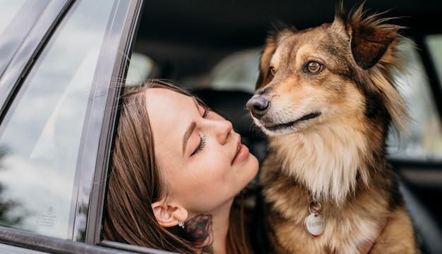 Frau, die ihren hund im auto betrachtet