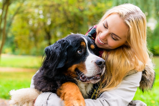 Frau, die ihren hund im herbstpark umfasst