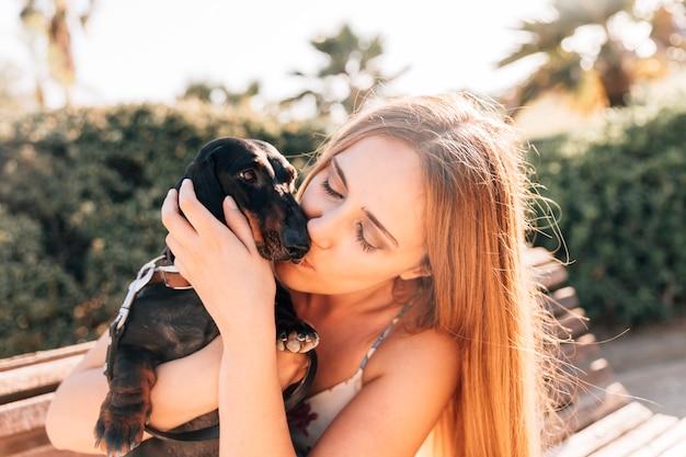 Frau, die ihren hund im park küsst
