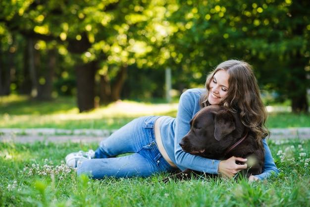 Frau, die ihren hund im park umarmt