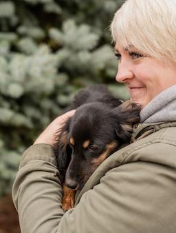 Frau, die ihren hund in einem park umarmt