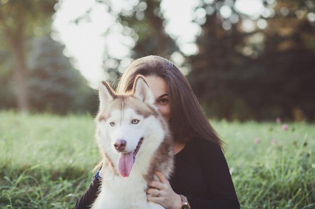 Frau, die ihren hund umarmt