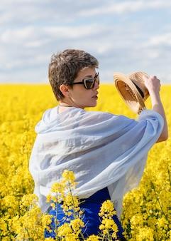 Frau, die ihren hut im gelben rapsfeld am warmen sonnigen frühlingstag abnimmt