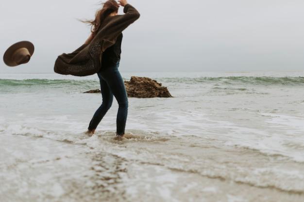 Frau, die ihren hut wegen des windes am strand fallenläßt