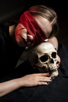Frau, die ihren kopf auf schädel liegt