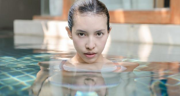 Frau, die ihren kopf aus dem wasser eines entspannenden urlaubs des pools hebt.