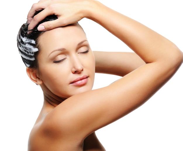 Frau, die ihren kopf mit shampoo wäscht