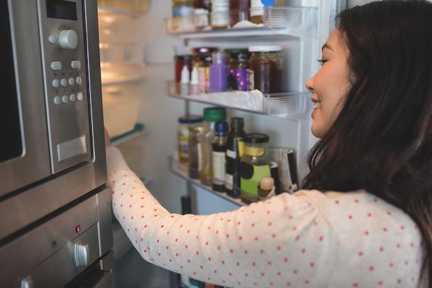 Frau, die ihren kühlschrank überprüft