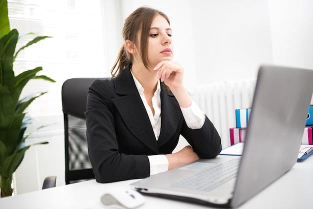 Frau, die ihren laptop bei der arbeit verwendet