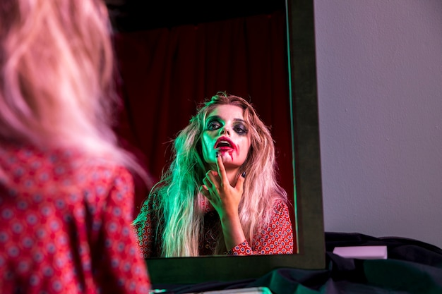 Frau, die ihren lippenstift für halloween-nacht repariert