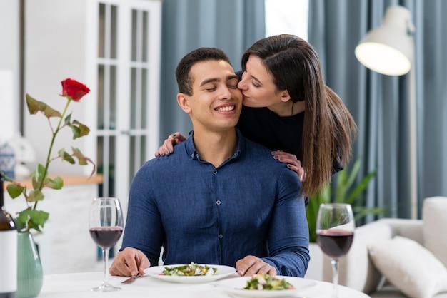 Frau, die ihren mann auf die wange küsst