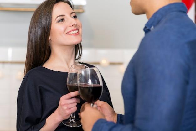 Frau, die ihren mann betrachtet, während sie ein glas wein hält