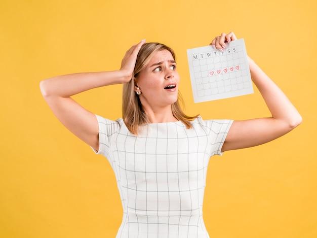 Frau, die ihren menstruationskalender mit furcht betrachtet