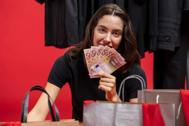 Frau, die ihren mund mit geld bedeckt