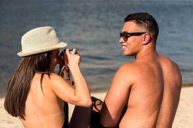 Frau, die ihren partner am strand fotografiert