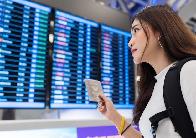 Frau, die ihren pass mit fluginformationsbrett im internationalen flughafen hält