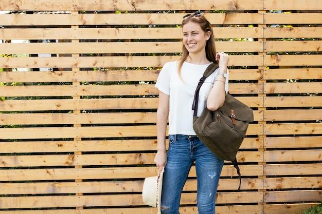Frau, die ihren rucksack hält und weg schaut