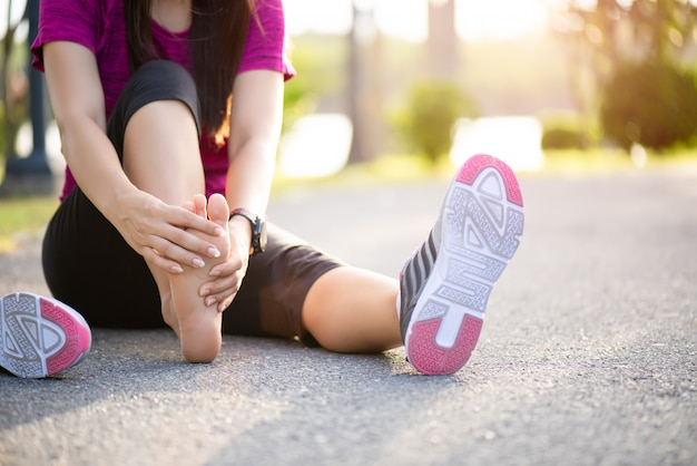Frau, die ihren schmerzlichen fuß beim trainieren massiert. laufen sportverletzung konzept.