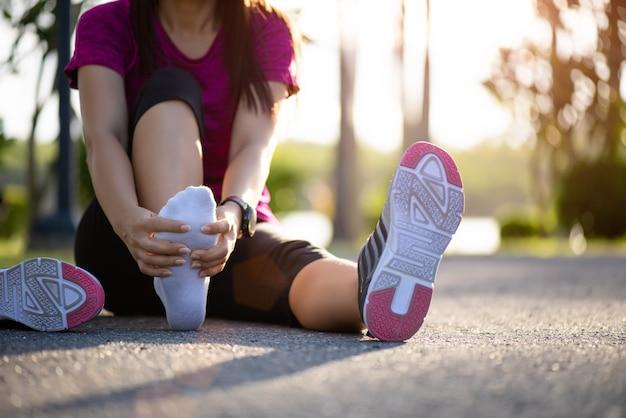 Frau, die ihren schmerzlichen fuß beim trainieren massiert. laufen sportverletzung.