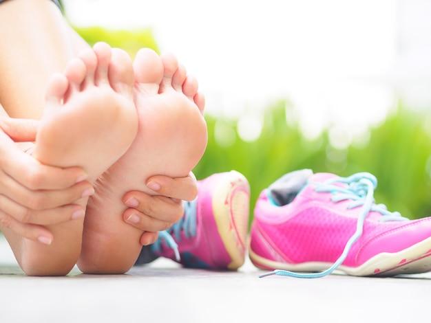 Frau, die ihren schmerzlichen fuß beim trainieren massiert. laufendes sportverletzungskonzept.