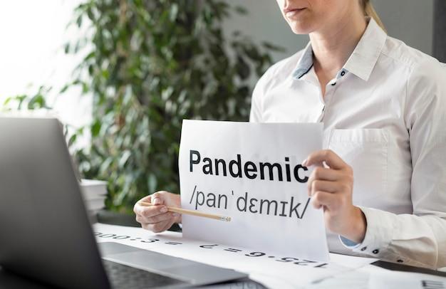 Frau, die ihren schülern die definition der pandemie beibringt