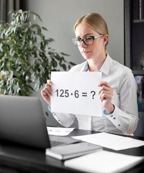 Frau, die ihren schülern einige multiplikationen lehrt