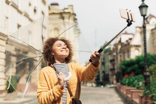 Frau, die ihren selfie-stock benutzt, um ein foto zu machen