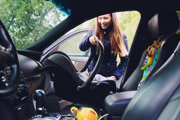 Frau, die ihren sohn auf einem kindersitz in einem auto befestigt.