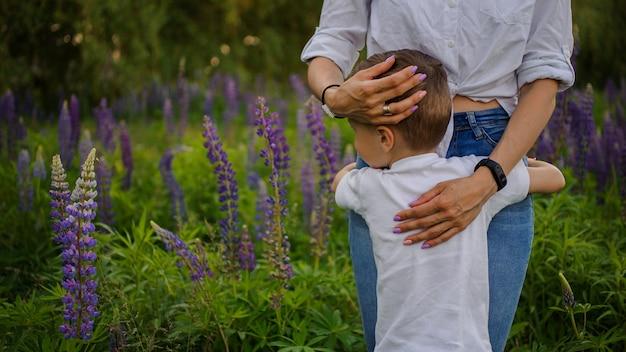 Frau, die ihren sohn steht auf dem purpurroten blumengebiet umarmt