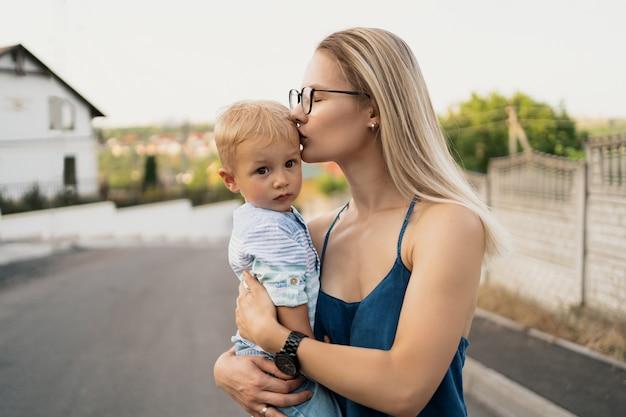 Frau, die ihren sohn trägt und auf seiner stirn küsst.